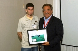 Brian Horn presents Dan Ryan a picture of himself with a Raytheon-built weapon in Iraq.